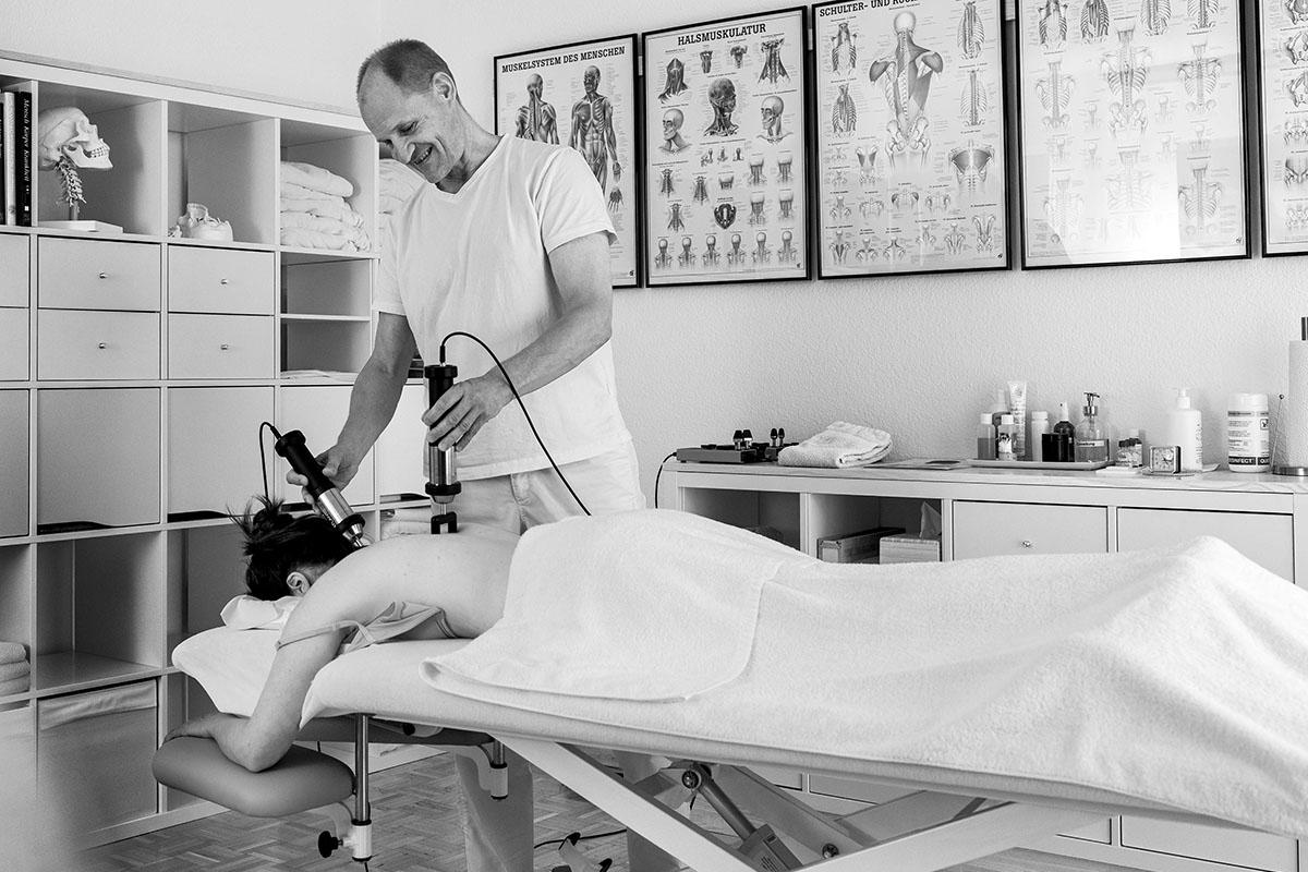 Therapeut richtet Atlas von Klientin mittels Vibrationsgerät